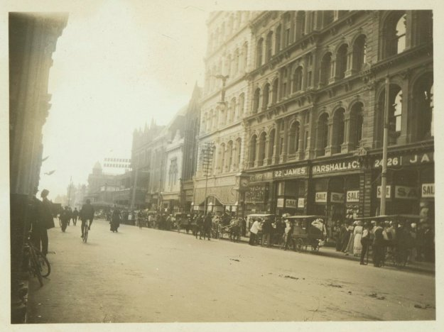 View looking down a street, with horse-drawn vehicles parked along the curb and pedestrians walking along the footpath. A sign on a building reads: 22. James Marshall & Co. 24-26.