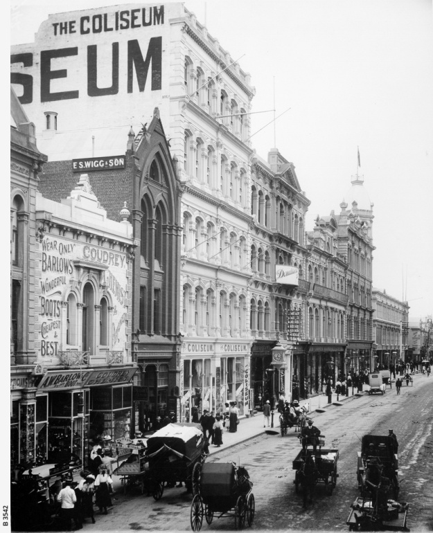Rundle Street with shops, department stores and street traffic. Some of the shops from the extreme left are: Barlows Shoes; Coudrey's Chemist; E.S.Wigg & Son, Stationers; The Coliseum, Donaldson's and James Marshall department stores. People are patronising the street fruit and vegetable barrows and strolling past the shop windows. There is one motor car to be seen amongst the horse-drawn traffic (in front of Marshall's). [On back of photograph] 'Rundle street, looking east from King William Street / Nov. 1909 / Near side of Barlow's (on extreme left) is 30 yards east of King William St.'