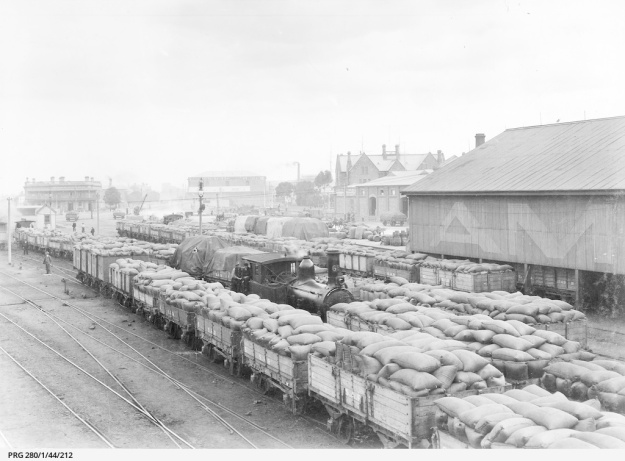 Railway trucks stacked with bagged grain waiting for transport from the railway station at Port Adelaide. Approximately 1910