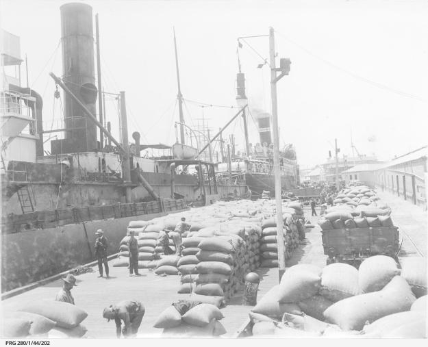 Men working with bagged grain waiting to be loaded on to cargo ships docked at Queen's wharf, Port Adelaide, South Australia. Approx. 1911