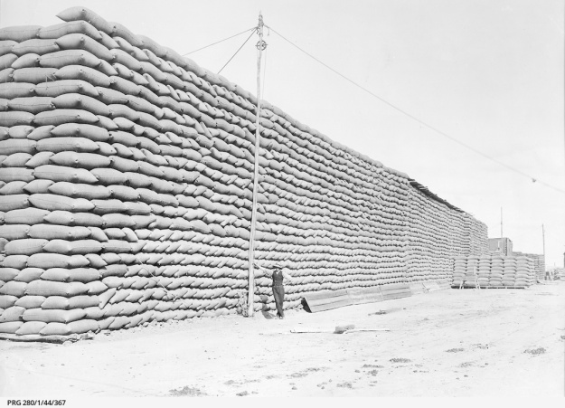 Large stacks of bagged wheat waiting for transportation from a receiving post in South Australia; exact location not known., Approximately1911.